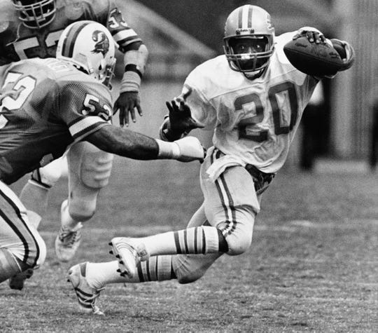 Detroit Lions Billy Sims tries to elude the grasp of Tampa Bay Buccaneer defender Scot Brantley in the second quarter but Sims was brought down after a short run in Tampa, Florida, Sept. 16, 1984. Brantley is No. 52 at left.