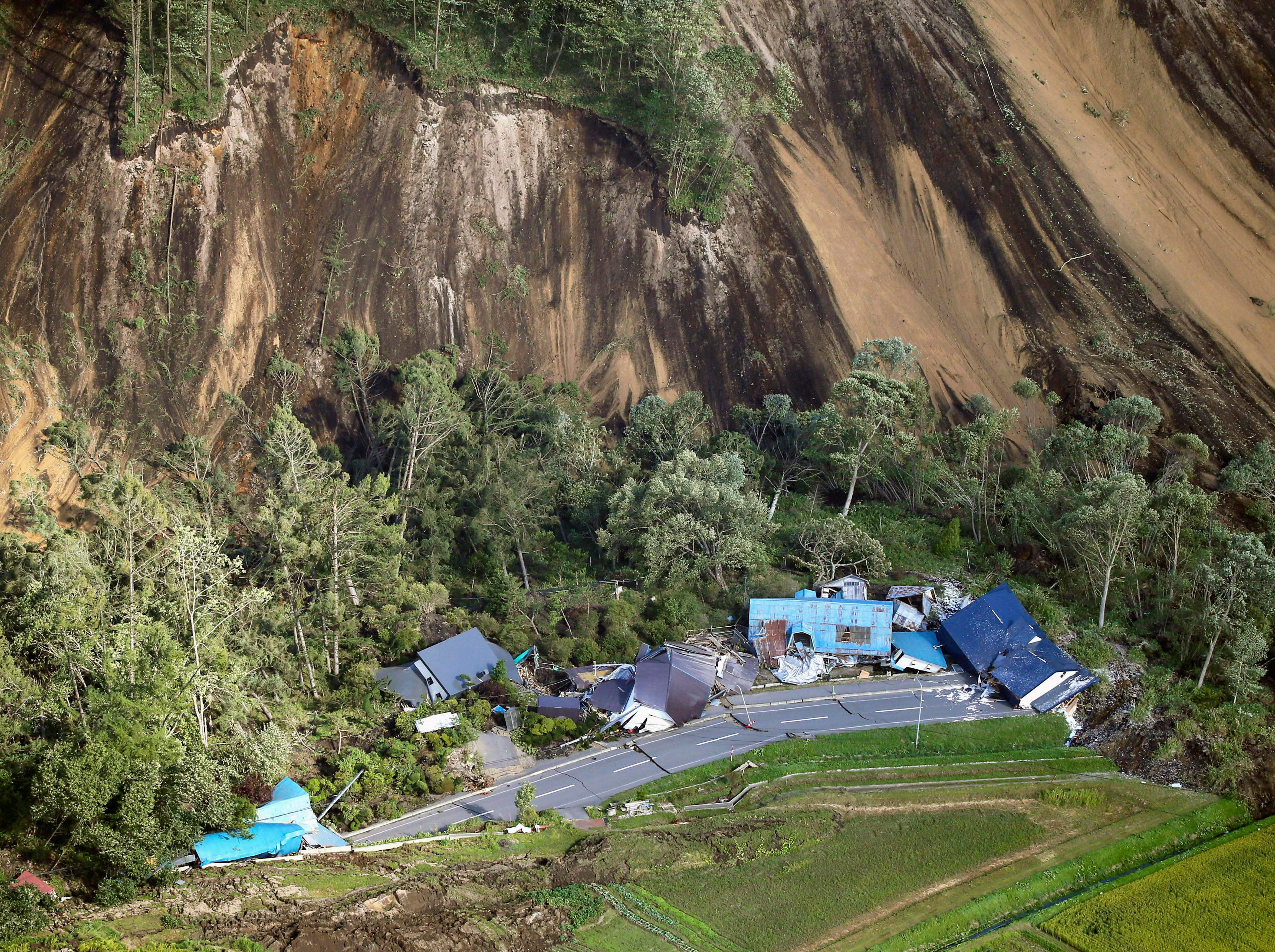 This aerial photo shows houses destroyed by a landslide after an earthquake in Atsuma town, Hokkaido, Japan, Thursday, Sept. 6, 2018. The powerful quake rocked Japan's northernmost main island of Hokkaido early Thursday, triggering landslides that crushed homes, knocked out power across the island, and forced a nuclear power plant to switch to a backup generator.