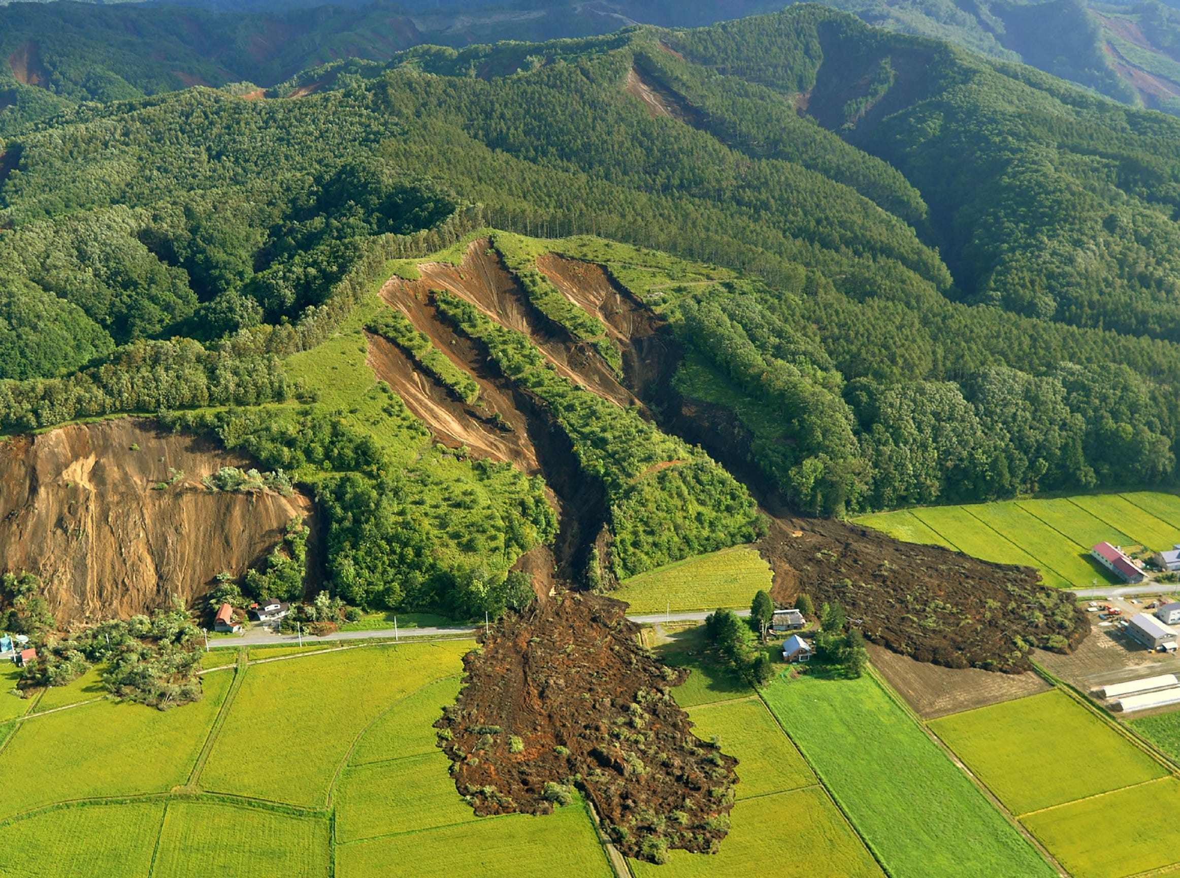 This picture shows an aerial view of a landslide in Atsuma town, Hokkaido prefecture on Sept. 6, 2018. A 6.6-magnitude quake hit the northern Japanese island of Hokkaido, triggering landslides, bringing down several houses and killing at least one person with several dozen missing.