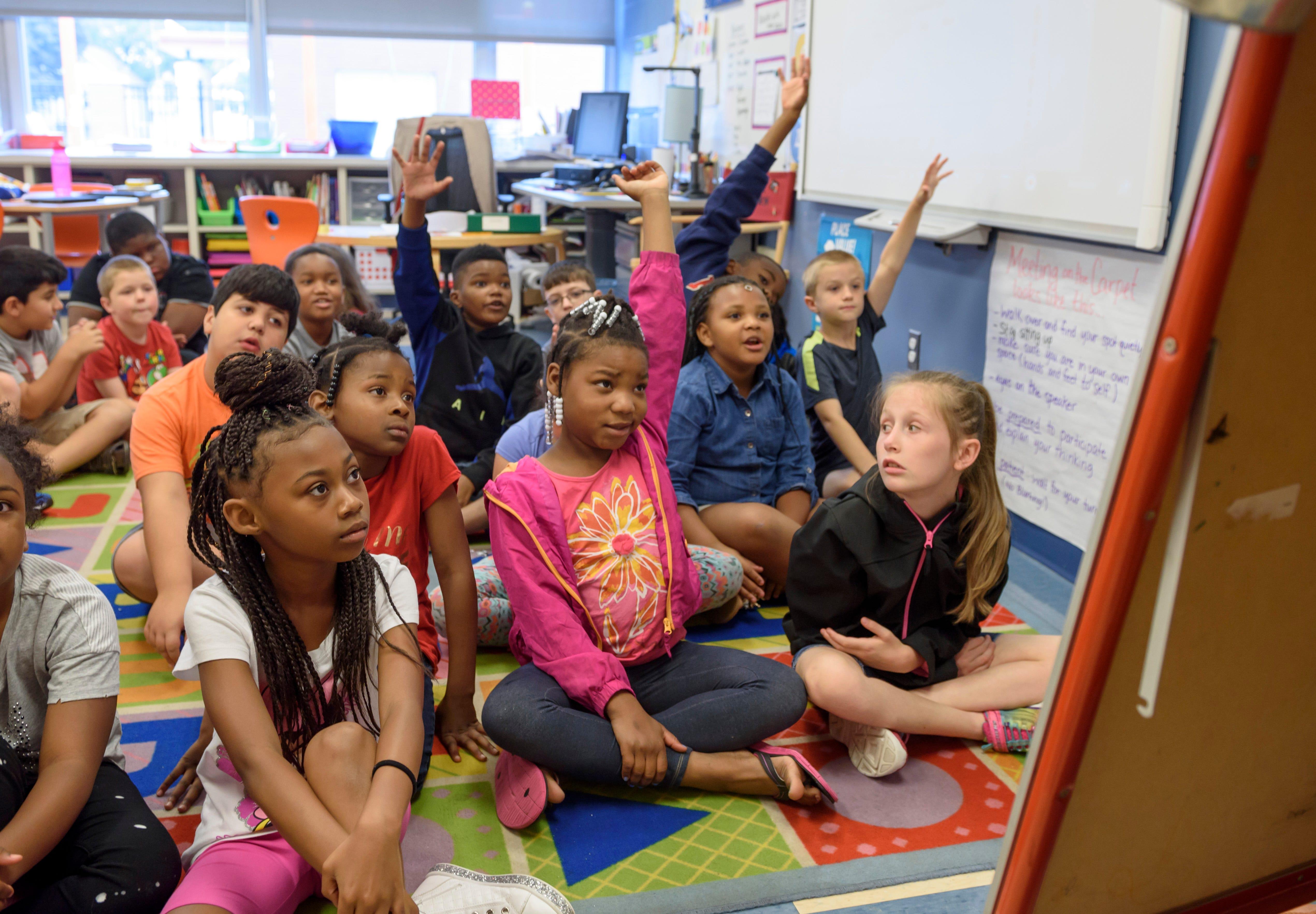 Students raise their hands during third grade teacher Celeste Brown's math class  at Madison Heights Elementary.