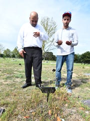 Mubarez Ahmed and family friend Aziz Hassan, who Ahmed said helped with the leg work in getting him released, pray at the grave marker of Ahmed's mother, Dahaba Ahmed, who died last year while he was still in prison.
