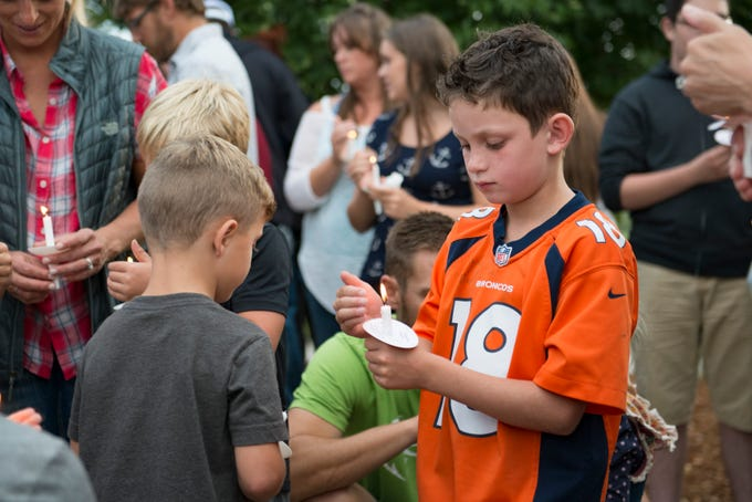 Beckett Yancey, 8, holds a candle during a vigil for Brycen Zerby, 8, at Eastman Park in Windsor on Wednesday, September 5, 2018. Zerby was killed Monday after being struck by a float during the Windsor Harvest Festival Parade.