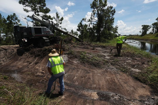 A crew working for Lee County clears a drainage ditch in Lehigh Acres on Wednesday 9/5/2018. The county is clearing areas that clogged during Hurricane Irma causing extensive flooding last year.