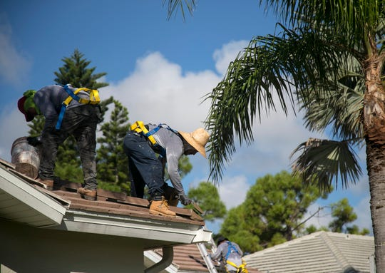 A crew from Kelly Roofing works on a new tile roof on a home in Bonita Springs on Thursday, Sept. 6, 2018.