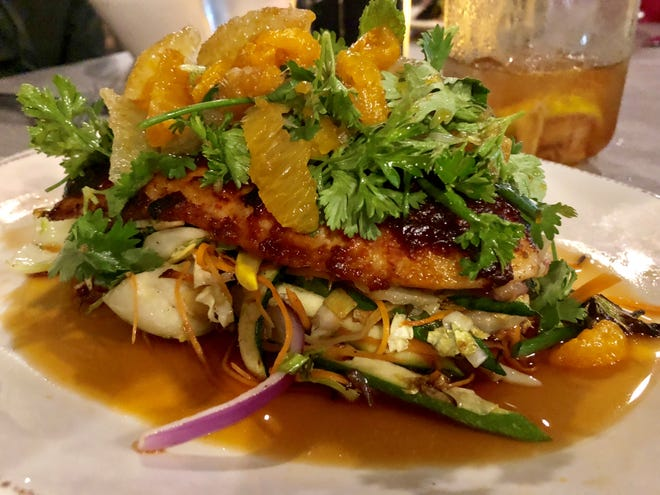 Chili-rubbed snapper is topped with a salad of cilantro, cashews, jalapenos and citrus. It's served atop stir-fried vegetables in a sweet ginger-soy sauce at The Jac.