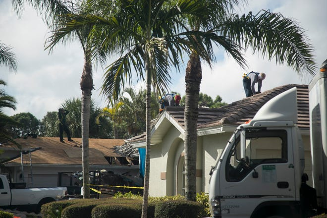 A crew from Kelly Roofing, at right, replaces a roof in Bonita Springs this month, while workers from another roofing company work on the house next door.