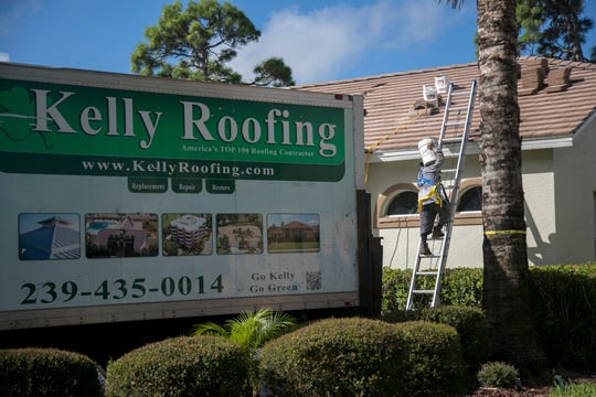 A worker from Kelly Roofing carries a bucket of cement onto a roof in Bonita Springs on Thursday, Sept. 6, 2018.