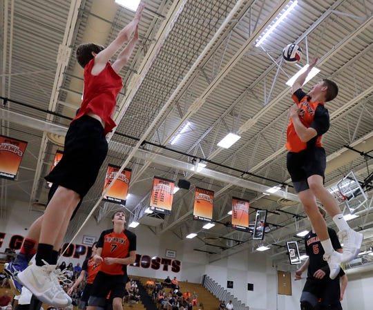 Kaukauna's Reis Schweiner, right, spikes against the block attempt by Landon Krause of Kimberly during a match last season.