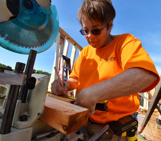 Volunteer Jacque Axland of Sturgeon Bay measures prepares to cut lumber during Door County Habitat For Humanity home build at 827 N. 6th Place, Sturgeon Bay, on Tuesday, Sept. 4, 2018. The house for Jacob and Amanda Purdy family will be the largest home in the county constructed by Habitat for Humanity.