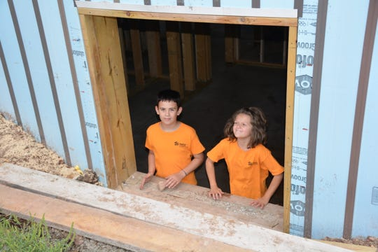 Jack Purdy, 11, and Alaina Purdy, 8, peer from one of the basement windows of their under-construction home, which is a project of Door County Habitat for Humanity Aug. 31, 2018.