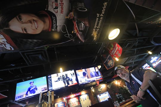Poison Ivy Pub owner Steve Quies sits at his bar near a large Danica Patrick poster. He's owned the sports bar in her hometown of Roscoe, Illinois, for 17 years.