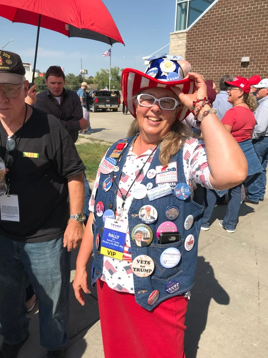 Susan Reneau wears a vest decorated with political buttons at the President Trump rally in Great Falls.