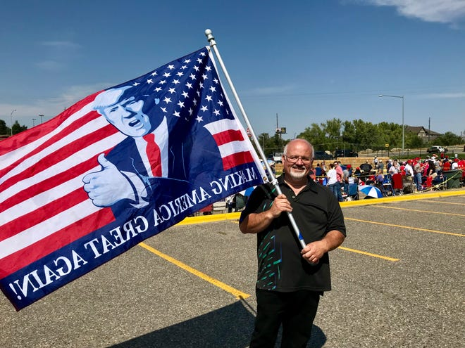 "Joe Parratore of Helena waves a Trump flag as he stands with a crowd of about 200 waiting at 1 p.m. for President Donald Trump's evening rally at Metra Park in Billings. He got in line at 7:30 a.m. ""I'm energized by this president,"" he said. ""It's going to be a blast."""