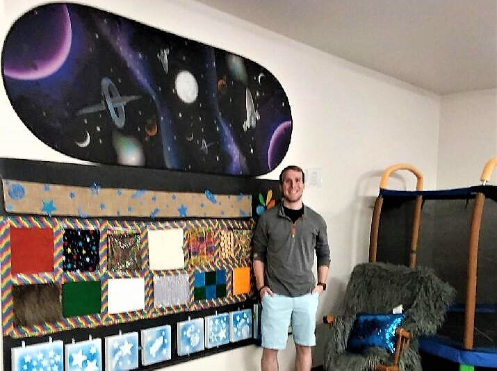 Joey McGuire poses by the sensory wall he created for Peace Place.