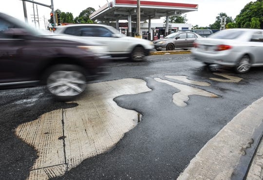 Motorists travel over worn out asphalt at the intersection of Routes 8, 10 and 16 in Barrigada on Thursday, Sept. 6, 2018. A project to resurface trouble spots on Route 1, 8, 8A 10 and 16 includes the intersection, according to the Department of Public Works.