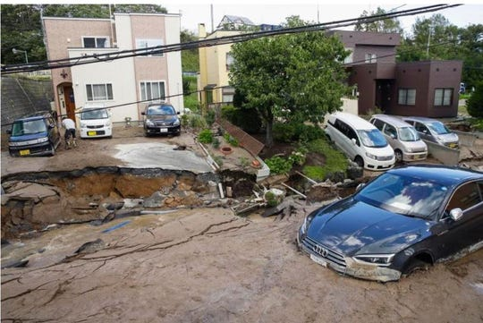Cars are stuck in mud covered road after an earthquake in Sapporo, Hokkaido, northern Japan, Thursday, Sept. 6, 2018. A powerful earthquake shook Japan's northernmost main island of Hokkaido early Thursday, causing landslides that crushed homes, knocking out power across the island.