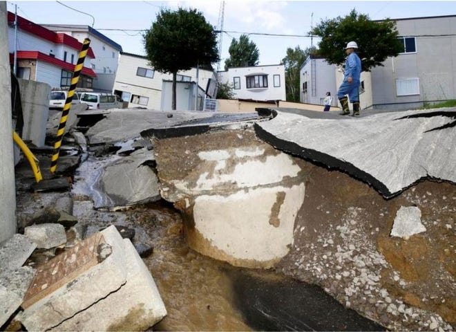 A road is damaged by an earthquake in Sapporo, Hokkaido, northern Japan, Thursday, Sept. 6, 2018. A powerful earthquake shook Japan's northernmost main island of Hokkaido early Thursday, causing landslides that crushed homes, knocking out power across the island. (Hiroki