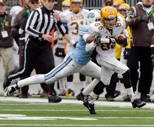 Kettering Alter's Chris Finke, right is tackled by Cleveland Benedictine's DeAndre' Penny during the third quarter of the Division IV state high school football championship game at Ohio Stadium, Dec. 5, 2014, in Columbus, Ohio.
