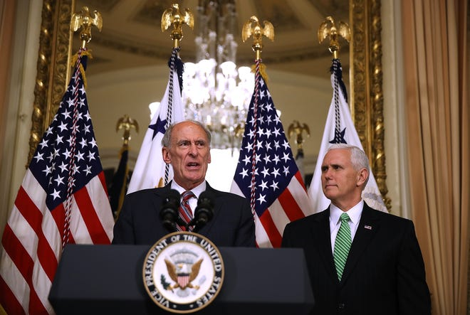 WASHINGTON, DC - MARCH 16:  New National Intelligence Director Dan Coats speaks to reporters as U.S. Vice President Mike Pence (R) looks on during Coats' swearing-in ceremony at the U.S. Capitol on March 16, 2017 in Washington, DC. The U.S. Senate  confirmed Coats 85-12 yesterday.  (Photo by Justin Sullivan/Getty Images)