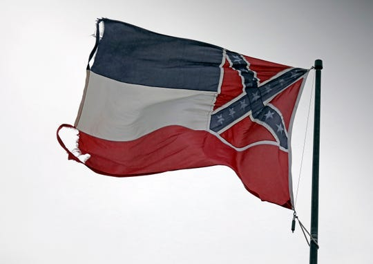 A tattered Mississippi state flag snaps in a strong wind.