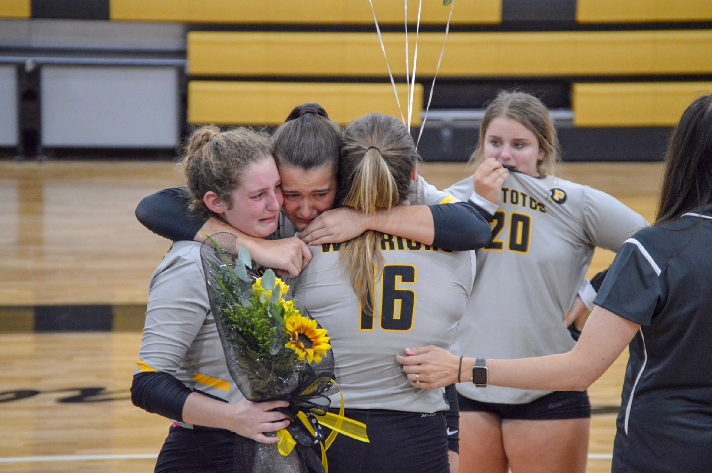 Taylor Hughes embraces her teammates and cries at New Hope High School after the final volleyball game of her high school career on Aug. 30, 2018. Her teammates brought her balloons and flowers.