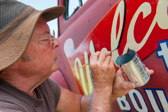 Paul Gore of Clinton hand paints the side of a 1947 Ford Super Deluxe Coupe while working on a project for the Main Street Clinton Boulevard Business District. His right wrist braces on his left for stability.His left hand holds a jagged-edged Diet Coke can with the top cut off. He uses it as a paint can.
