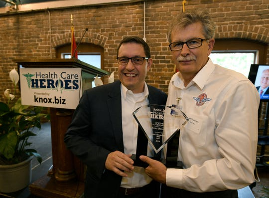 President of the Knoxville News Sentinel Frank Rosamond, left, presents the lifetime achievement award to Jeff Eastman, CEO of Remote Area Medical, accepting on behalf of RAM founder Stan Brock, at the Knox.biz Health Care Heroes luncheon at the Foundry on Thursday, Sept. 6, 2018.