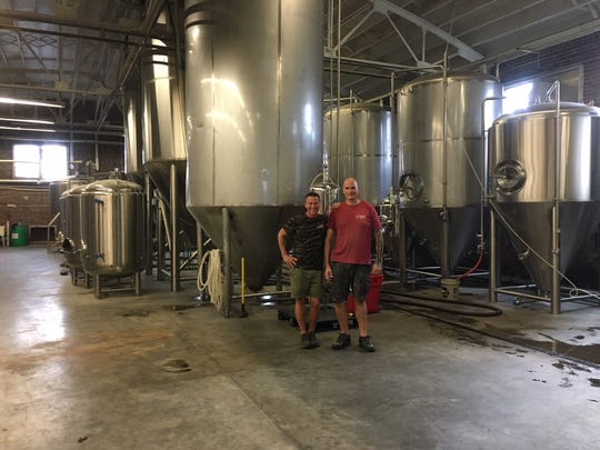 """Marty Velas, owner of Fanatic Brewing Company, and Justin Shaver, assistant brewer, strike a pose in the cavernous brewing room where the Sept. 15 party will take place. Stephanie Richter is a fan of the brew, which she describes as """"beer for people who don't think they like beer."""""""