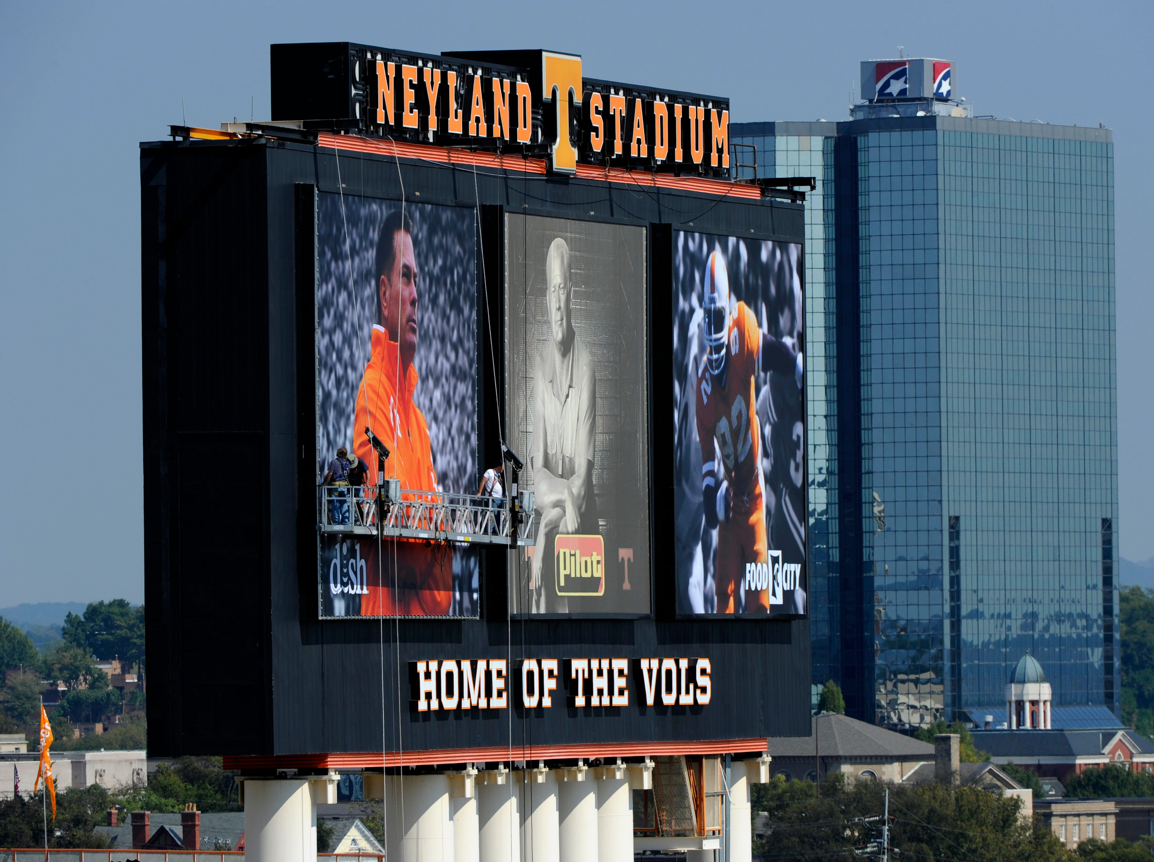 Workers securing a photo of Tennessee coach Butch Jones along side Gen. Neyland and Reggie White on the jumbotron at Neyland Stadium Thursday, Oct. 2, 2014.