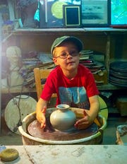 Levi Gilpin, 7 years old in this photo, describes himself as a sculptor. Here he works on a piece at Joppa Mountain Pottery.
