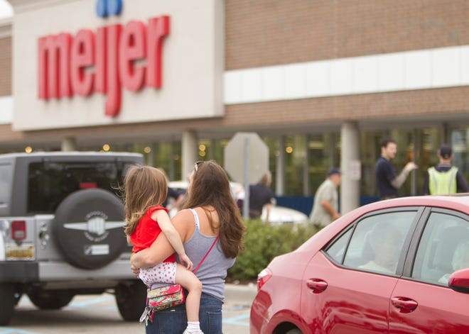Meijer customers and employees outside the Brighton Meijer store, which was evacuated Thursday morning, Sept. 6, 2018 due to a gas leak inside the store.