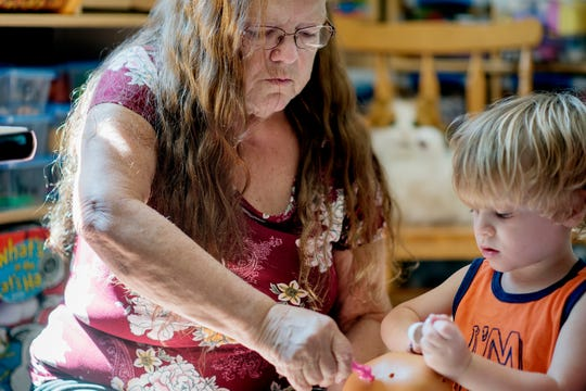 Child care provider Cindi Brown plays with 3-year-old Easton Arts on Wednesday, Sept. 5, 2018, in St. Johns. Brown, who has been in the child care business for 23 years, says she can no longer care for foster parents' children after severe delays in payments from the state. Brown cares for 12 children, including two foster children who are not pictured.