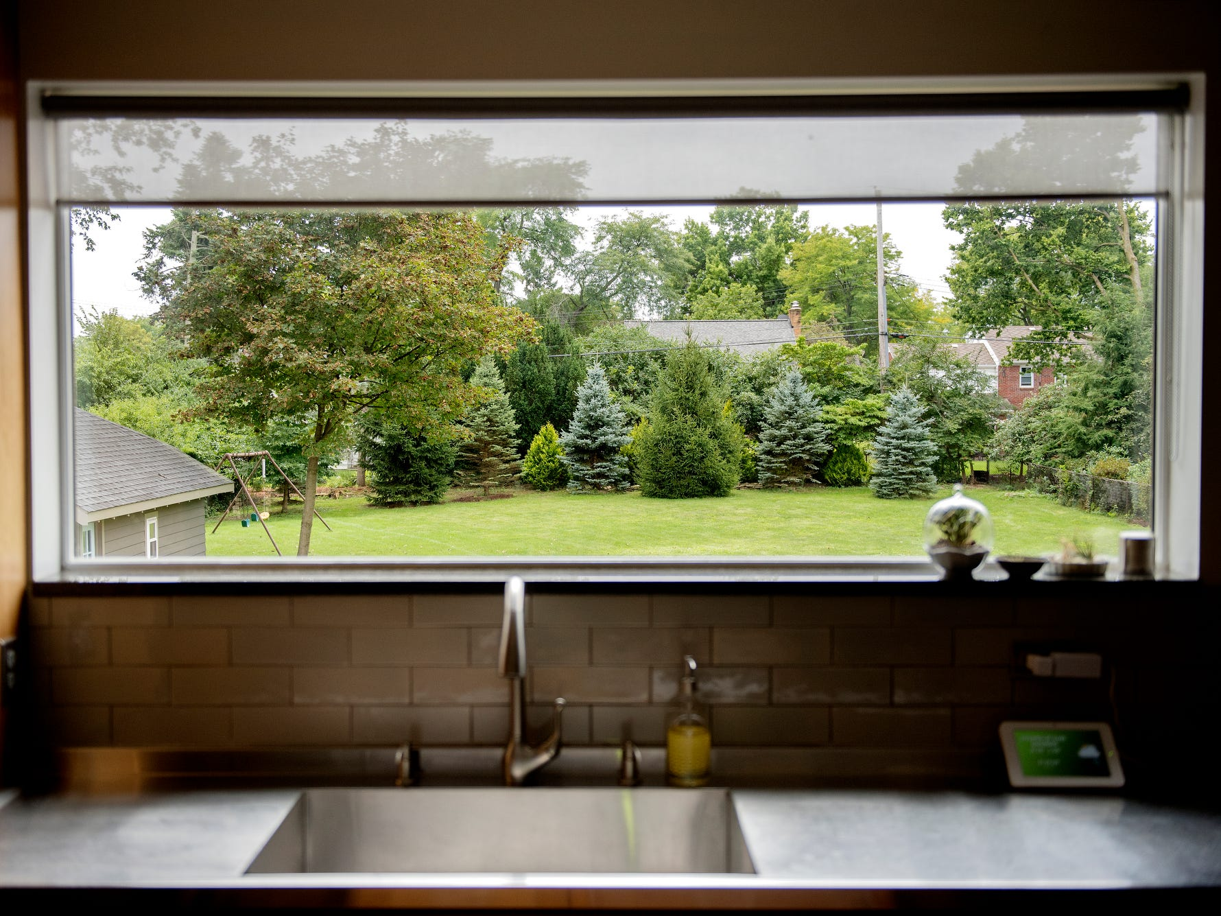 A large window facing the backyard is positioned in front of the main kitchen sink at the Purchases' Moores River Drive home on Thursday, Sept. 5, 2018, Lansing. The home is one of five homes that will be featured on the Sept. 16 Lansing Area Historical Home Tour.