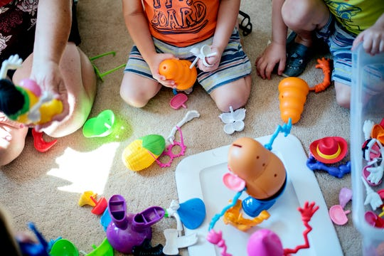 Child care provider Cindi Brown, left, plays with 3-year-old Easton Arts, center, and his twin brother, Landon,on Wednesday, Sept. 5, 2018, in St. Johns. Brown, who has been in the child care business for 23 years, says she can no longer care for foster parents' children after severe delays in payments from the state. Brown cares for a dozen children, including two foster children who are not pictured.