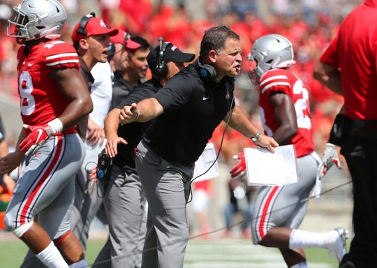 Ohio State defensive coordinator Greg Schiano congratulates his defense during the second quarter of the Buckeyes' season opener against Oregon State.