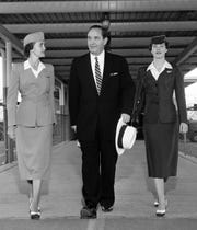 Arkansas Gov. Orval Faubus changes planes in Memphis for Little Rock with the aid of two airline stewardesses, Miss Marilyn Fredrick (Left) of Delta C&S and Miss Jo Ann Martin of Braniff.  Governor Faubus flew to Memphis from Chicago where he attended the National Governors' Conference in September 1955.