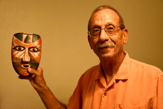Artist Peter Sottong with one of 14 masks he makes, featured in Collier County marketing efforts. Sottong has created replicas of the Key Marco Cat and a variety of Calusa masks, ahead of the Cat's anticipated return to Marco Island at the end of this year.
