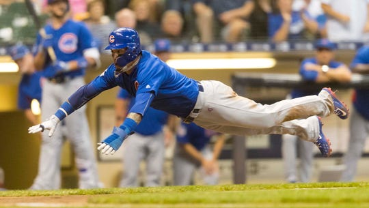 Chicago Cubs shortstop Javier Baez (9) dives into home during the fourth inning against the Milwaukee Brewers at Miller Park.