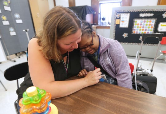 Christina Johnson (right) gets a hug from special education teacher Courtney Baran in her transition skills class at Riverside University High School.