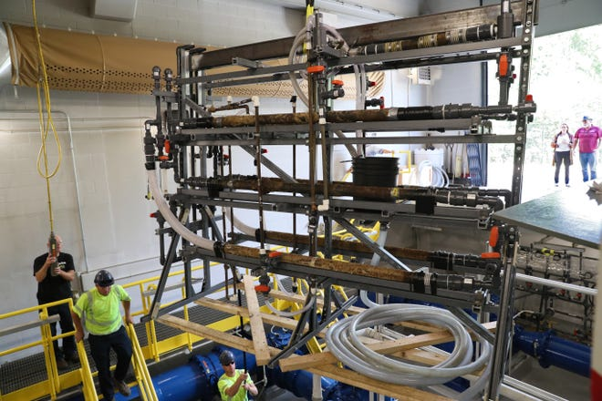 Waukesha Water Utility and Milwaukee Water Works employees place a set of Waukesha residential and municipal water pipes into the Grange Pumping Station on the southwest side of Milwaukee for testing with Lake Michigan water. For the next eight months, Milwaukee water will flow through the series of copper pipes with lead solder taken from a Waukesha home and iron service lines removed from the Waukesha distribution system.