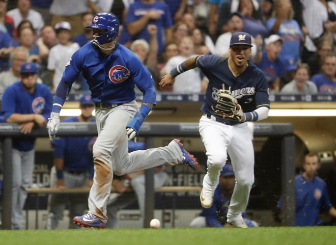 Javier Baez of the Cubs sprints home to score as Orlando Arcia chases down an errant throw from Brewers centerfielder Lorenzo Cain in the fourth inning.