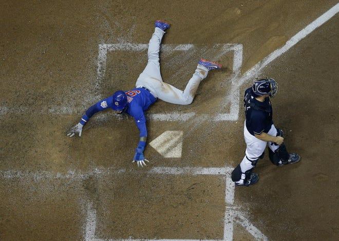 Javier Baez scores past Brewers catcher Erik Kratz during the Cubs' four-run fourth inning Wednesday night at Miller Park.