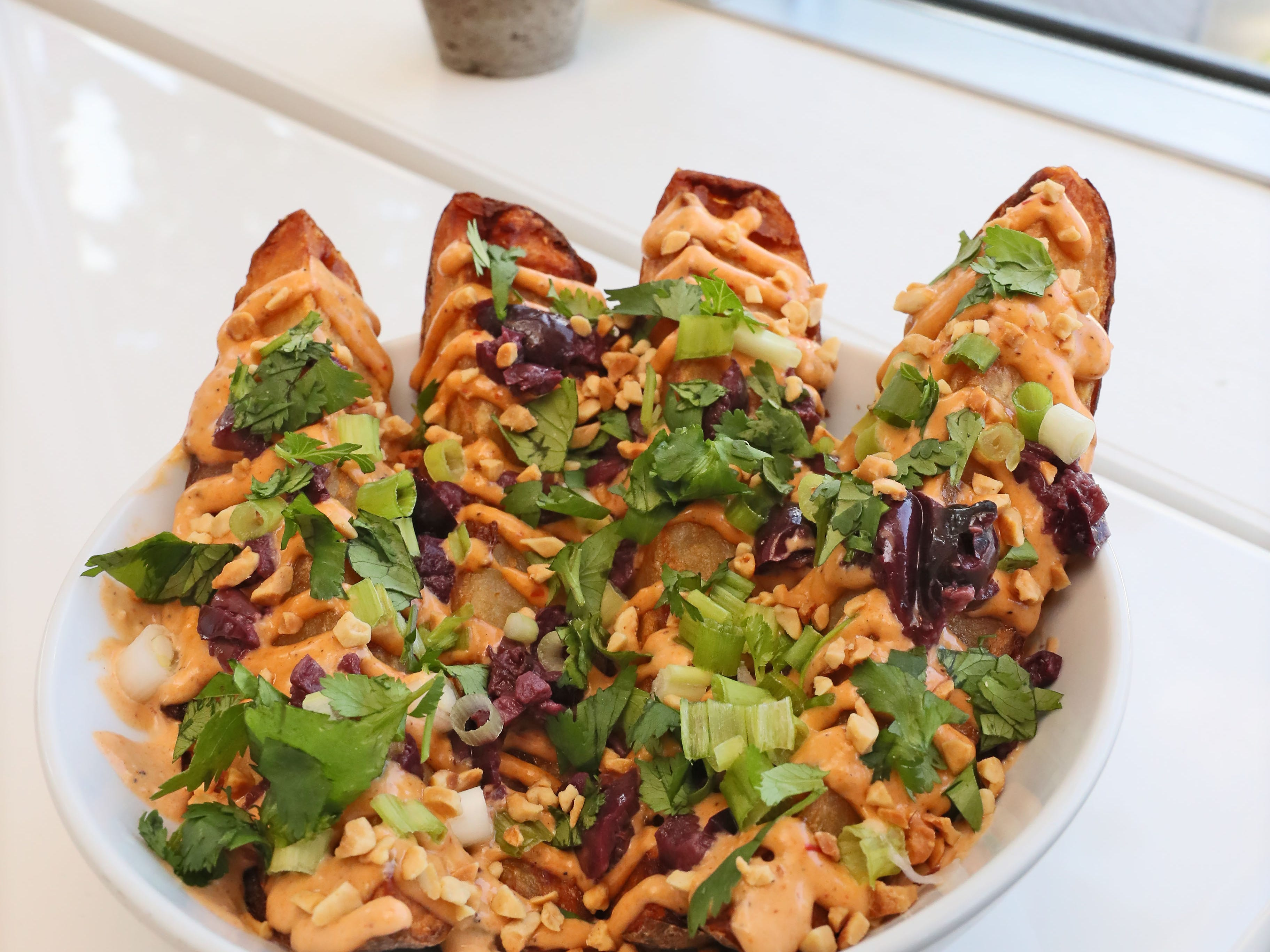 Celesta, a vegan restaurant at 1978 N. Farwell Avenue, offers a shareable plate of Lima fries, garnished in remoulade, green onion, cilantro, peanuts and olives.