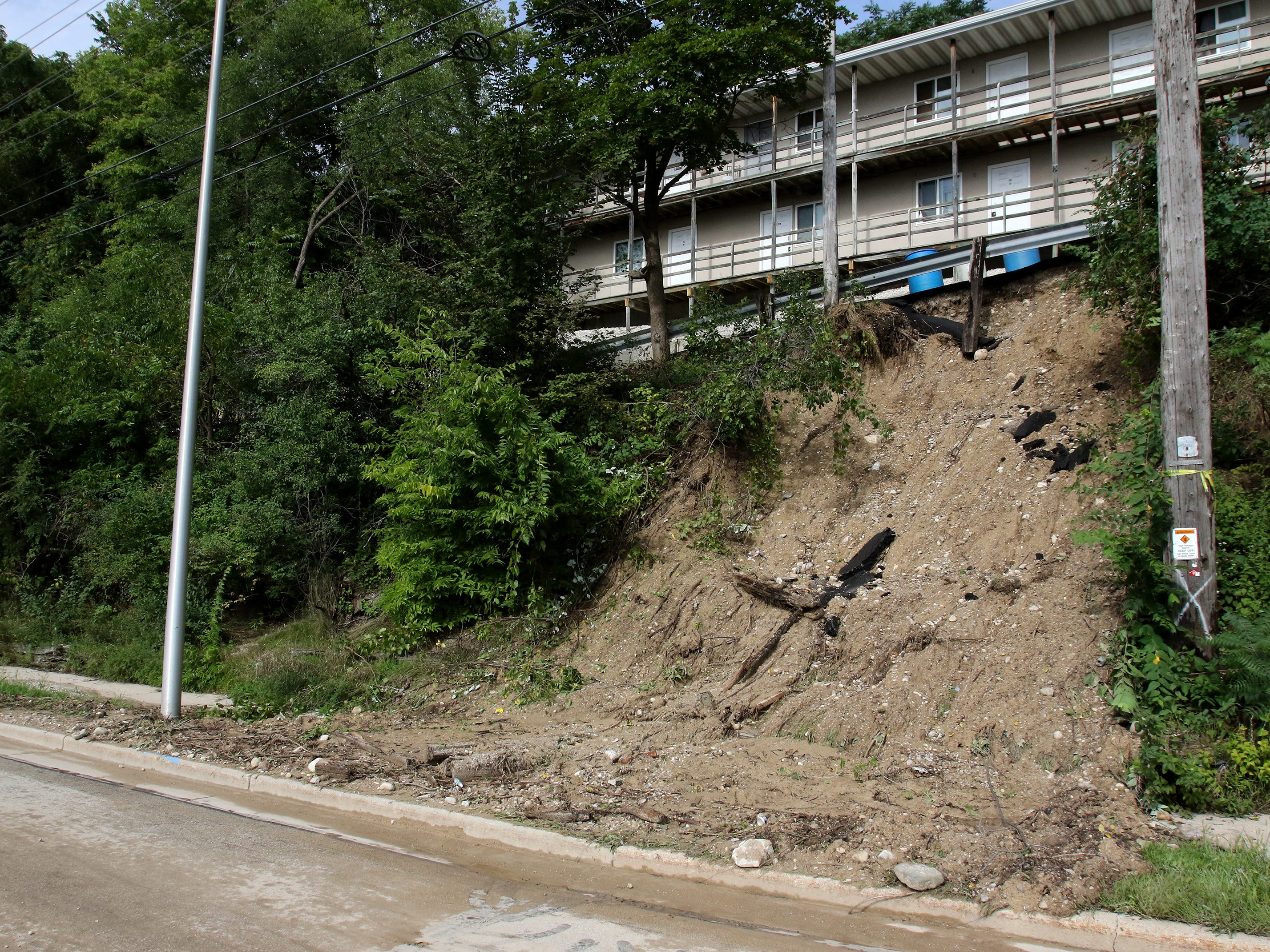 A guard rail standard base to an apartment parking lot is exposed when mud and debris from a steep hill flowed across Pewaukee Road where it merges with East North Street on Sept. 6 forcing the closure of Pewaukee Road between East North Road and Buena Vista Avenue.