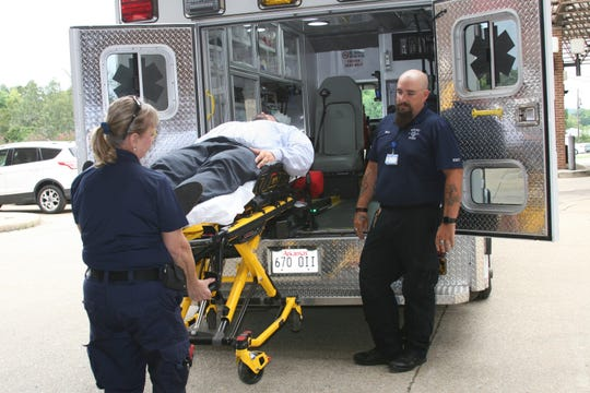 Baxter Regional Medical Center Director of Marketing Tobias Pugsley volunteers to represent a patient on an automated stretcher. The stretcher unit uses hydraulics to lift and lower patients to and from the ambulance, decreasing the chances of injury to the patient and to paramedics like Nancy Jones and Brian Cox, featured in the photo. Baxter Regional Hospital Foundation is campaigning to raise $200,000 to replace two aging ambulances from BMRC's current fleet.