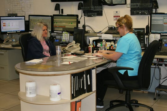 Mariona Porter, supervisor of Baxter Regional Medical Center's emergency medical dispatch (EMD) department shares patient information with emergency medical dispatcher Becky Katakis between calls. BMRC Director of Ambulance Services Gerald Cantrell and Supervisor of Ambulance Services Christopher Fry said BMRC's dual dispatch system is an essential element in a patient's survival rate when being transported to the hospital.