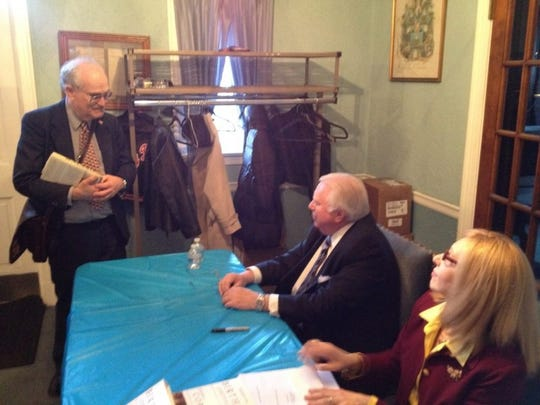 Jerome Corsi, sitting, signs books during a public appearance in Morristown in 2012.