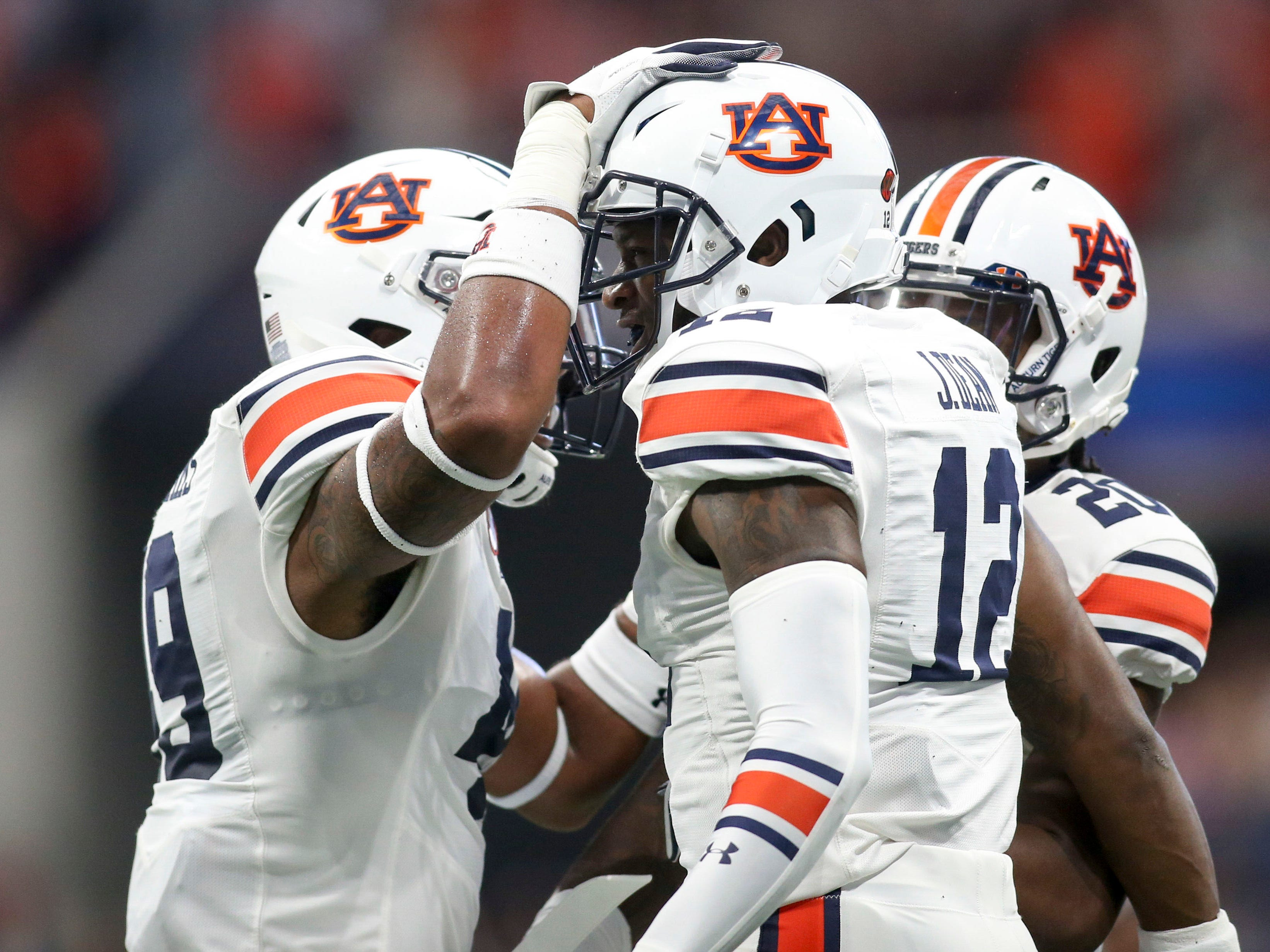 Auburn cornerback Jamel Dean (12) celebrates after an interception with linebacker Darrell Williams (49) and defensive back Jeremiah Dinson (20) against Washington on Sept. 1, 2018, in Atlanta.