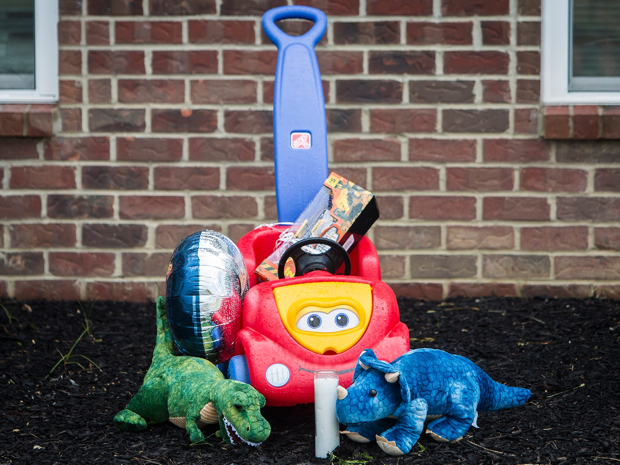 A memorial is positioned outside of a residence at Salem Place Apartments in Daleville near where two-year-old Jaxon Stults was found dead in a vehicle late Wednesday night.
