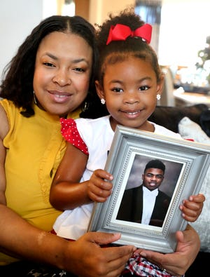 Michelle Roberts holds her daughter Maya Roberts,4, who holds a picture of Michelle Roberts son and MayaÕs brother Michael Lee Roper on Thursday, Sept. 6, 2018. Roper was shot and killed this past Saturday in Murfreesboro.
